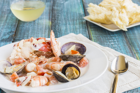Seafood stew made with lobster, crab, shrimp and clams cooked in coconut milk with tomatoes and onions