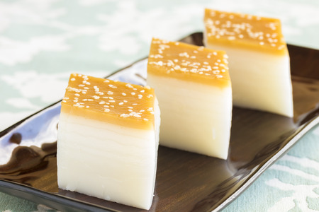 three layered: Layered Chinese rice cakes with sesame seed topping Stock Photo