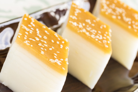 Layered Chinese rice cakes with sesame seed topping Stock Photo