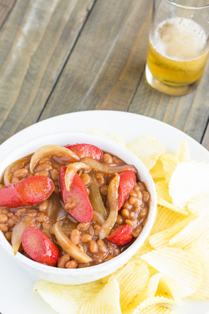 Brown sugar pork and beans with Maui sweet onions and Hawaiian paprika hot dogs, served with potato chips
