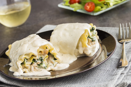 smothered: Sauteed taro leaves and kalua pork rolled in lasagna noodles smothered with haupia bechamel sauce, a common meal for families in Hawaii