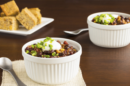 cornbread: Vegetarian chili made with onions, tomatoes, corn, kidney and black beans, topped with sour cream and diced jalapeno, served with cornbread