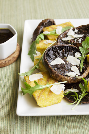 Balsamic marinated portobello mushrooms with grilled slices of polenta, arugula and shaved parmesan, with a balsamic reduction photo