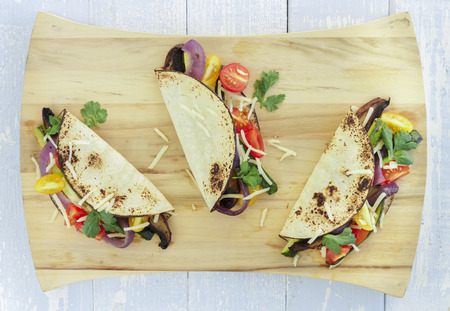 Tacos filled with roasted portobello mushrooms, zucchini and purple onions, with cherry tomatoes, cilantro and monterrey jack cheese photo