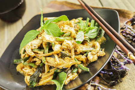 long bean: Chicken stir-fried with onion, garlic, curry paste, long bean, bamboo shoots, and coconut milk, served with Thai basil Stock Photo