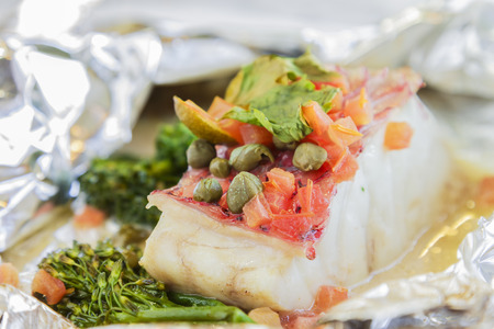 Hawaiian pink snapper cooked in a white wine butter sauce with broccolini, and spices Stock Photo