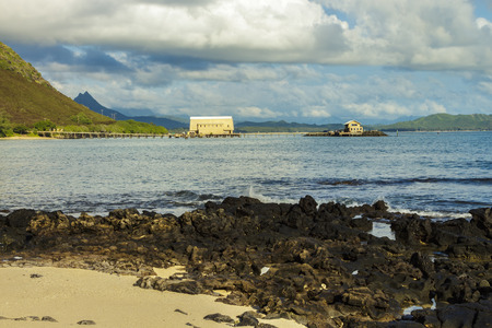 View of Makai Research Pier in Waimanalo Bay with Koolau mountain range in the distance on Oahu, Hawaii Stock Photo