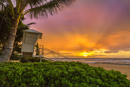 A misty, windy sunrise makes a soft colorful sky at a lifeguard stand at Sandy Beach on Oahu, Hawaii