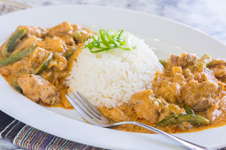 Chicken thighs and green bell peppers in panang curry sauce, served with rice Stock Photo