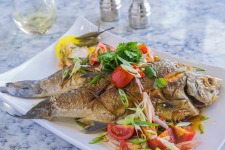 Fried whole fish served with tomato salad