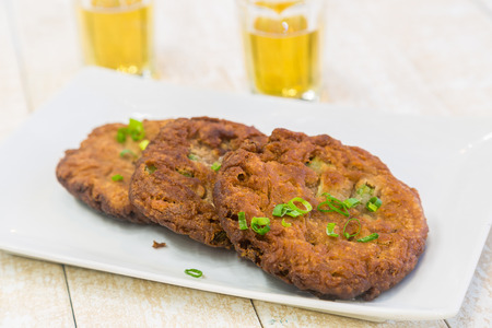 poi: Crispy fried poi and vegetable patties topped with green onions