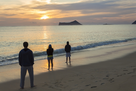 appreciating: Three people starting the day appreciating a beautiful sunrise at Waimanalo Bay on Oahu, Hawaii Stock Photo