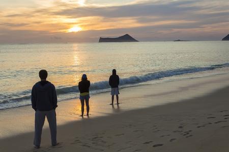 appreciating: Three people starting the day appreciating a beautiful sunrise at Waimanalo Bay on Oahu, Hawaii Stock Photo