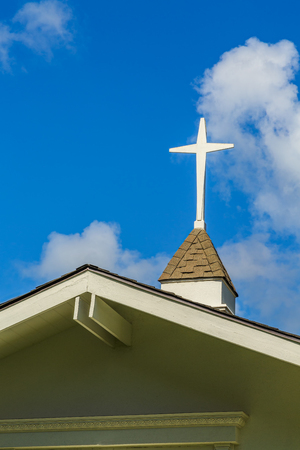 steeple: The steeple and cross on the roof of a small chapel Stock Photo