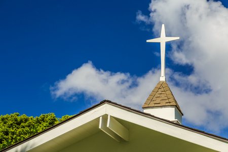 church building: The steeple and cross on the roof of a small chapel Stock Photo