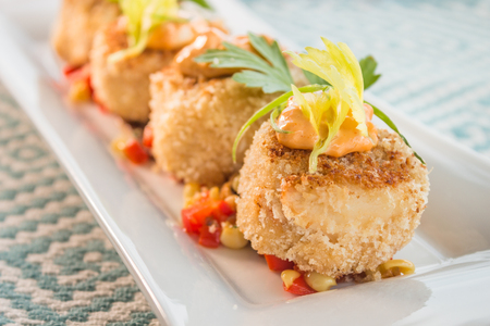 Breaded crab cakes served on top of corn relish and topped with sauce Archivio Fotografico
