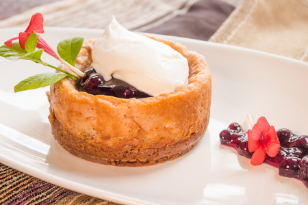 poi: Poi cheesecake with coconut crust topped with blueberry sauce and whipped cream Stock Photo