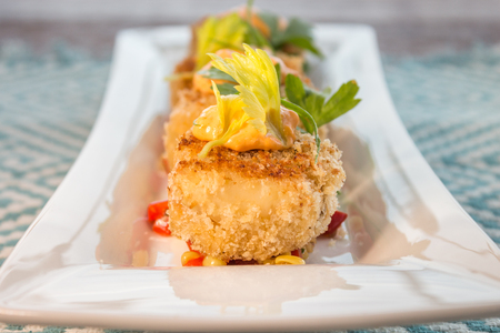 crab: Breaded crab cakes served on top of corn relish and topped with sauce Stock Photo