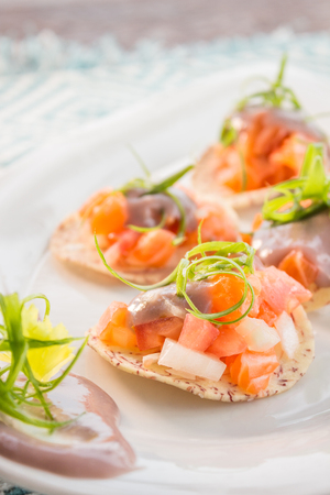 Salmon ceviche served on taro chips topped with poi and green onion garnish