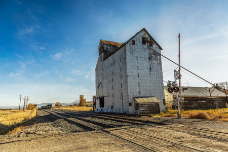 An old abandoned grainery at the edge of railroad tracks in Montana Stock Photo
