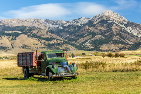 An old truck in a field at the foot of the Bridger mountain range in Belgrade, Montana