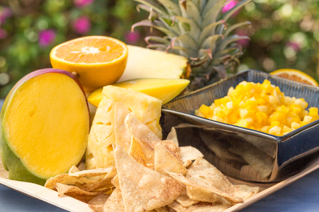 A sweet snack of pineapple, mango, orange and papaya salsa, served with cinnamon tortilla chips Stock Photo