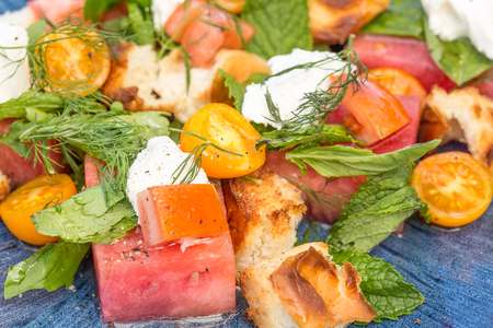 Bread salad with watermelon, tomato, basil and goat cheese