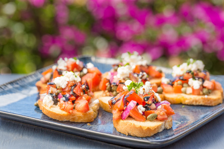 A mix of tomatoes, purple onions and capers with goat cheese and balsamic reduction on toast Stock Photo
