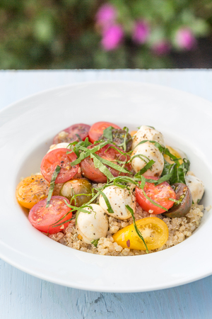 A healthy salad of cherry tomatoes and mozzarella on a bed of quinoa