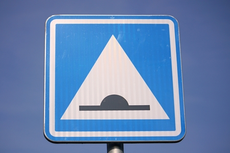 law breaker: Speed bump road sign against blue sky Stock Photo