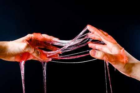 Hands stretch the slime poured on them on a black background