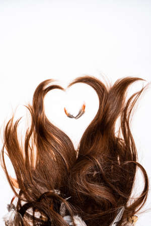 Heart-shaped hair with a pen in the center on a white background