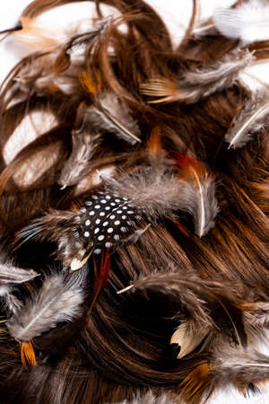 Hair mixed with feathers lie on a white table