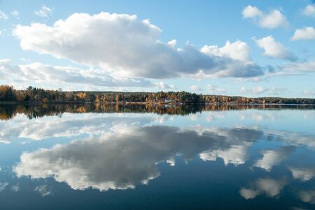 A beautiful autumn day on one of the lakes in Sweden with a beautiful reflection of the golden trees . Stock Photo