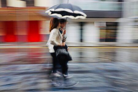 tourist with umbrella walking on the street in Bilbao city Spain, rainy days
