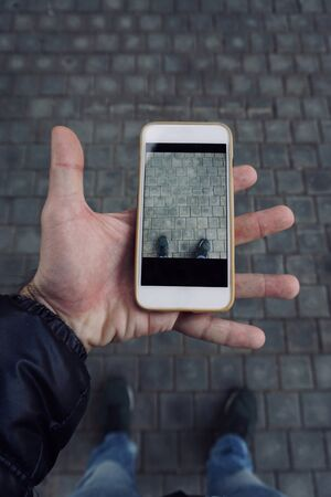 man hand with a smartphone on the street Фото со стока