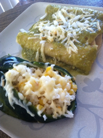 Enchilada plate. Green enchiladas topped with cheese served with a green chile stuffed with rice
