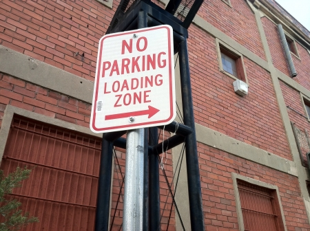 No parking sign with red letters.