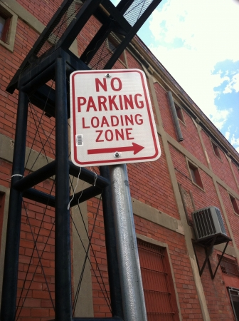 White no parking loading zone with red letters.