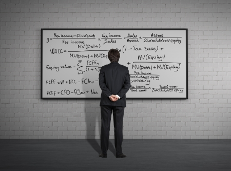 Businessman standing in front of board with formulas photo