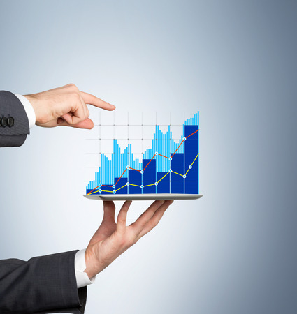 specific: Businessman showing a specific point in the tablet projection graph