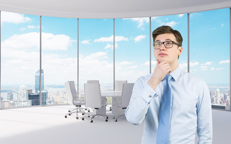 thinking young businessman standing in modern office photo