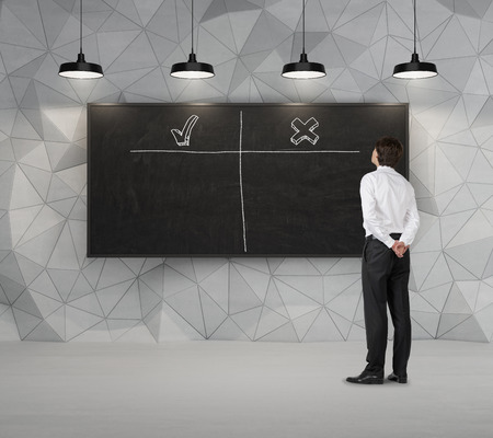 disadvantages: businessman looking at blackboard with analysis advantages and disadvantages