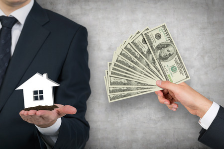 house shopping: businessmans hand giving money for housing on  gray background