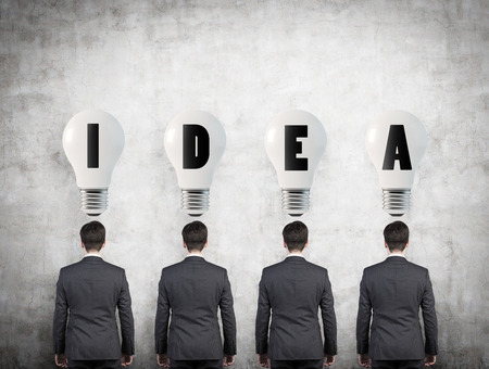 four businessman standing with bulb over head photo