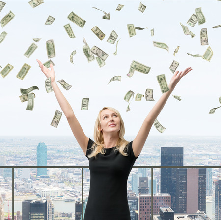 money savings: woman with hands up on falling dollars bills Stock Photo