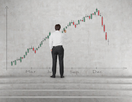 gripping bars: businessman drawing candlestick chart on wall in office