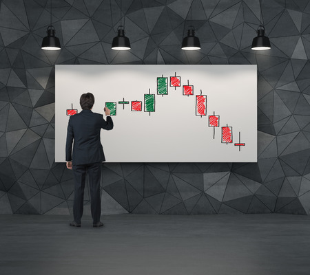 businessman drawing color candlestick chart on placard
