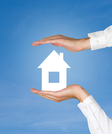 small paper: hands  holding paper house on blue background