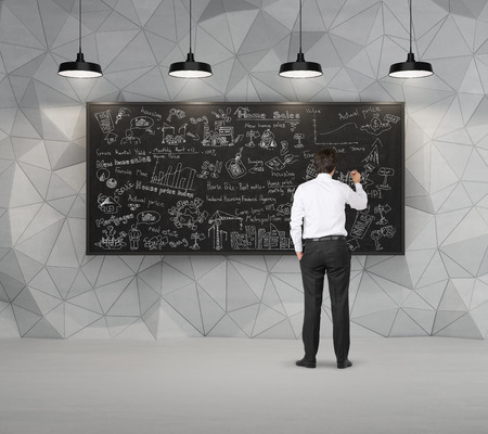 aspirations ideas: businessman in room drawing business concept on  blackboard